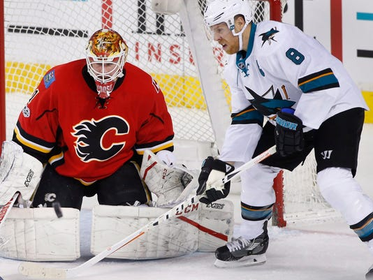 San Jose Sharks' Joe Pavelski, right, looks for a rebound as Calgary Flames goalie Brian Elliott makes a save  during the first period of an NHL hockey game Friday, March 31, 2017, in Calgary, Alberta. (Larry MacDougal/The Canadian Press via AP)