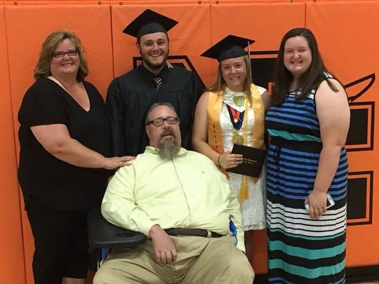 Mike Heck Jr. (center) poses after graduation with