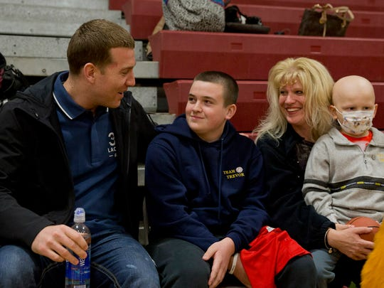 Jill Kwatkowski (second from right) talks with Chicago White Sox and Toms River native Todd Frazier (left) with sons Justin (second from left), and Trevor (right) as during a fundraiser for Trevor, who has bone cancer, Thursday night at Central Regional.