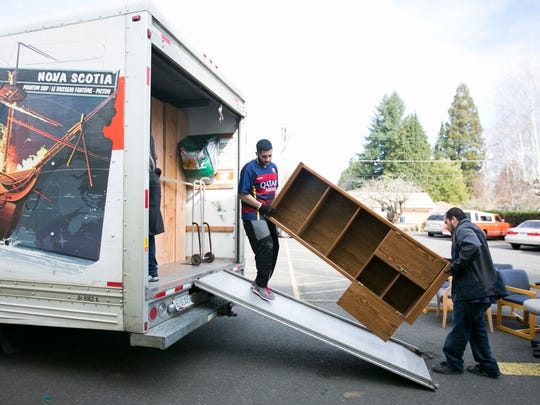 Gonzalo Ruiz, left, and Jose Tolento load a bookshelf into a truck outside the old home of the Mid-Valley Literacy Center on Wednesday. The two work for Cabinet Door Service, which donated the time of several employees to help with the move. The literacy center has previously partnered with the cabinet manufacturer to teach language skills to the company's employees.