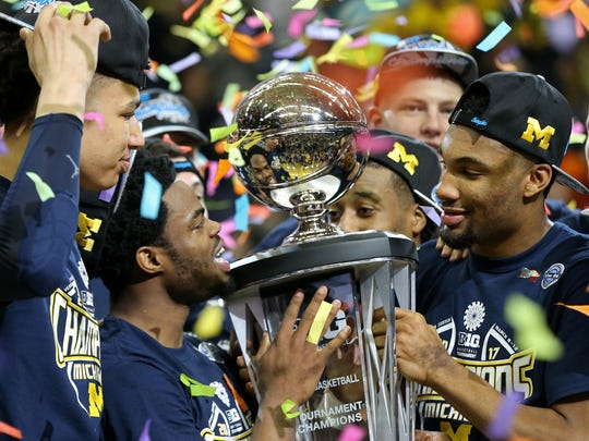 Mar 12, 2017; Washington, DC, USA; Michigan Wolverines guard Derrick Walton Jr. (L) and Wolverines guard Zak Irvin (R) celebrate with the championship trophy after their game against the Wisconsin Badgers during the Big Ten Conference Tournament championship game at Verizon Center. The Wolverines won 71-56.