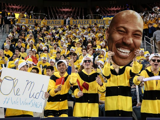 Michigan fans holds a sign of #WeWantSHEA, referring to Ole Miss transfer QB Shea Patterson, a picture of LaVar Ball, and Chinese flags before a basketball game against UCLA at Crisler Center in Ann Arbor, Saturday, Dec. 9, 2017.