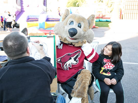 Howler from the Arizona Coyotes sits with a young guest at a Walk With Me event.