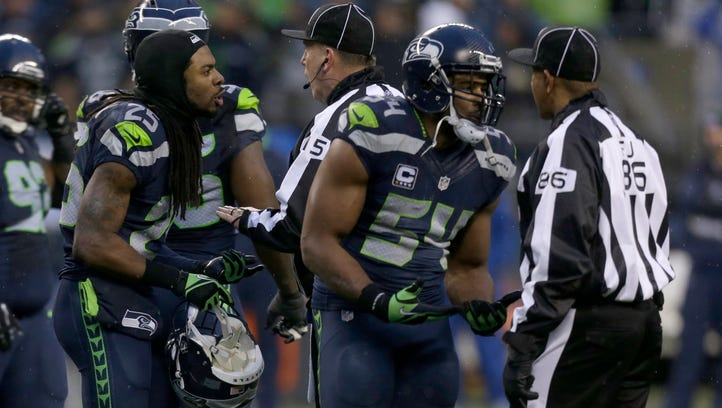 Seattle Seahawks cornerback Richard Sherman, left, and Seattle Seahawks middle linebacker Bobby Wagner talk with field judge field judge Jimmy Buchanan during the second half of an NFL football game, Sunday, Dec. 27, 2015, in Seattle.