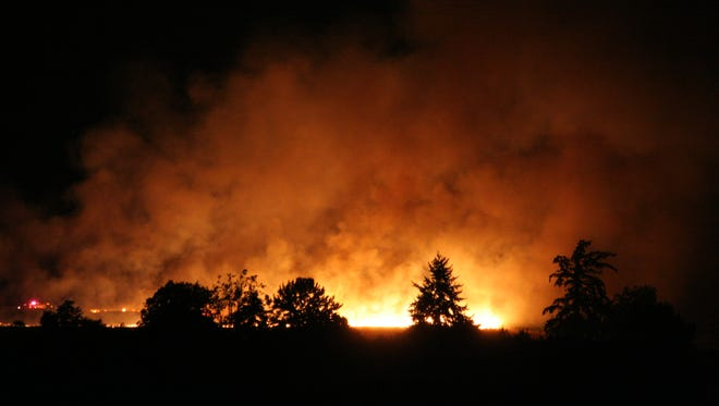 A wheat field fire off Wallace Road NW lights up the night.