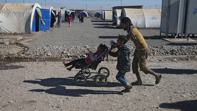 An Iraqi man who fled the fighting between Islamic State militants and the Iraqi forces, carries a handicapped girl at a camp for internally displaced people, in Khazer east of Mosul, Iraq, Monday, Nov. 21, 2016.