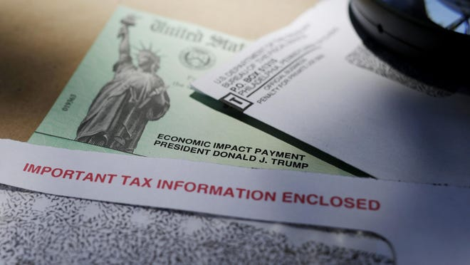 FILE - In this April 23, 2020, file photo,  a stimulus check issued by the IRS to help combat the adverse economic effects of the COVID-19 outbreak can be seen