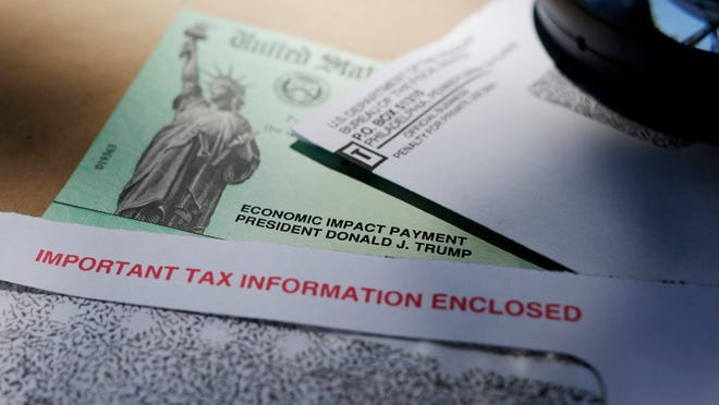 In this April 23, 2020, photo, President Donald Trump's name is seen on a stimulus check issued by the IRS to help combat the adverse economic effects of the COVID-19 outbreak, in San Antonio. The US government has distributed about 130 million economic impact payments to taxpayers in less than 30 days. The IRS anticipates sending more than 150 million payments as part of a massive coronavirus rescue package. The distribution has had some hiccups, including an overwhelmed website, payments to deceased taxpayers and money sent to inactive accounts.