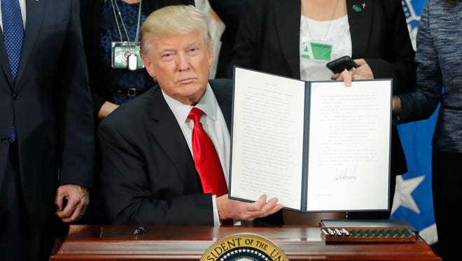 President Donald Trump holds up an executive order for border security and immigration enforcement improvements. (AP Photo/Pablo Martinez Monsivais)