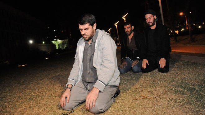Three freed Guantanamo Bay detainees, who were resettled in Uruguay, pray during their protest outside the U.S. embassy in Montevideo, Uruguay, Friday, April 24, 2015. From left are Omar Abdelahdi Faraj and Ali Husain Shaaban, both of Syria, and Adel bin Muhammad El Ouerghi of Tunisia.