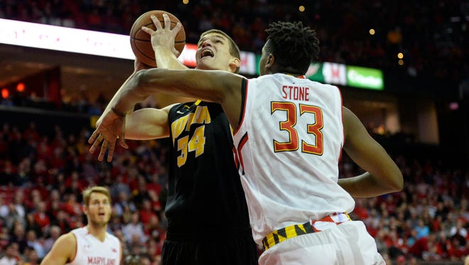 Iowa's Adam Woodbury, left, goes against Maryland's Diamond Stone during Thursday's 74-68 win by the Terrapins in College Park, Md., in a battle of top-10 teams.