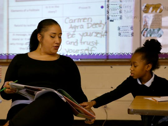 Second grade teacher Linda Baez and student Taleah Chandler work on lessons learned throughout a story the class was reading at Eugenio Maria de Hostos Charter School 9.