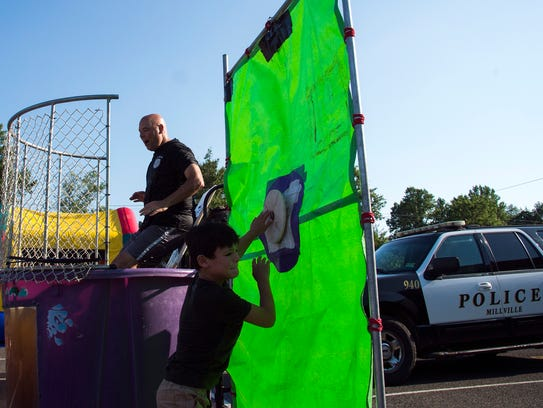 A young boy hits a button to dunk Rick Kott of the