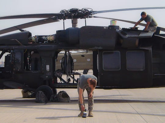 Sgt. Michael Nelson, upper right, works on a Black Hawk helicopter during a deployment to Afghanistan with the 159th Combat Aviation Brigade, 101st Airborne Division.