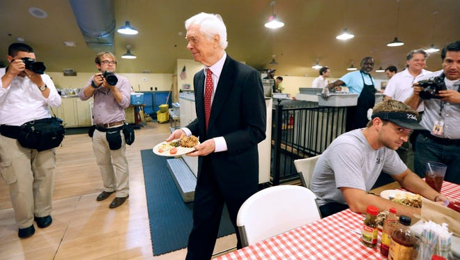 A patron of Mama Hamil's Restaurant in Madison reacts to photographers as U.S. Sen. Thad Cochran, R-Miss., carries his lunch for a semi-private lunch with friends and supporters while photographers record the event Tuesday. Cochran is in a runoff against state Sen. Chris McDaniel for the GOP nomination for senate.