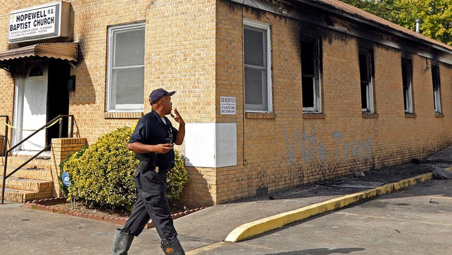 "A state fire marshal investigates the fire-damaged Hopewell Missionary Baptist Church in Greenville, Miss., on Wednesday, Nov. 2, 2016. ""Vote Trump"" was spray painted on an outside wall of the historically black church."