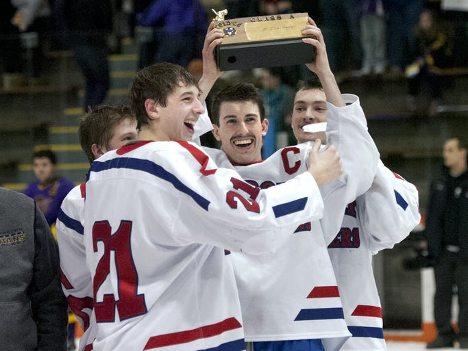 Fairport captains, including Pat Doud, center, and Quinn Wiedemer (21) hoist the championship trophy following the Class A Championship game played at RIT's Frank Ritter Ice Arena on Sunday, Feb. 23, 2014.  No. 3 seed Fairport won the Class A title with a 3-0 win over No. 4 seed Greece Thunder.