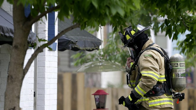 A Neenah-Menasha firefighter heads into an apartment building on the corner of South Lake Street and Adams Street Friday, June 12, 2015, in Neenah, Wis.  Danny Damiani/Post-Crescent Media