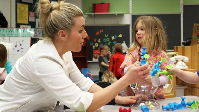 Kelly Kerr, an early education teacher at Huron Valley Schools' Apollo Center in Highland Township, works on a play-based learning project with Skylar Roberts.