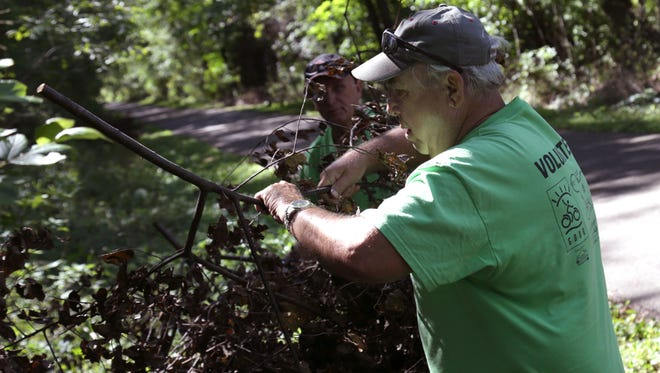 Steve Reynolds and Terry White help clear brush off the Richland B&O Trail in Lexington on Tuesday. Both are volunteers from the Mid-Ohio Bikers group, who help maintain the trail.