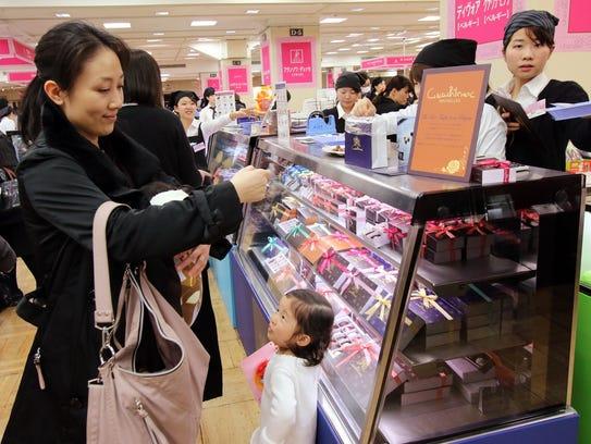 Women buy chocolates before Valentine's Day at Tokyo's