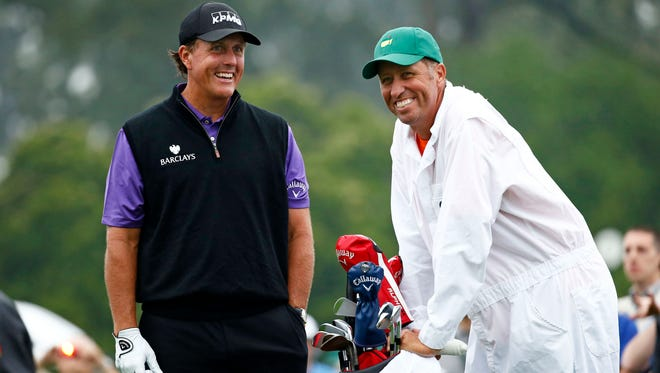 "Phil Mickelson and caddie Jim ""Bones"" Mackay wait to tee off on the 1st hole during a practice round April 7."