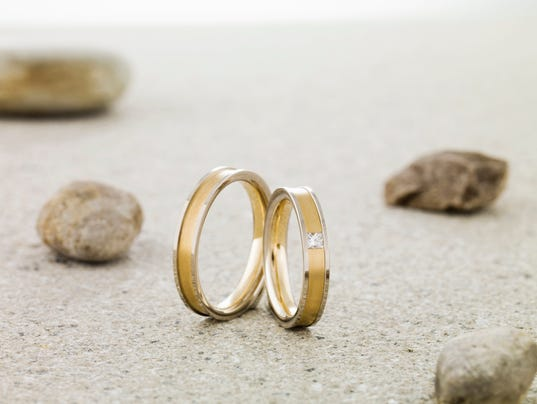 Wedding rings balanced on stone