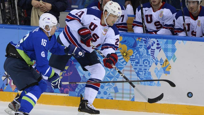 Slovenia's Ales Music (left) fights with the puck with James van Riemsdyk during an Olympic ice hockey game in 2014.