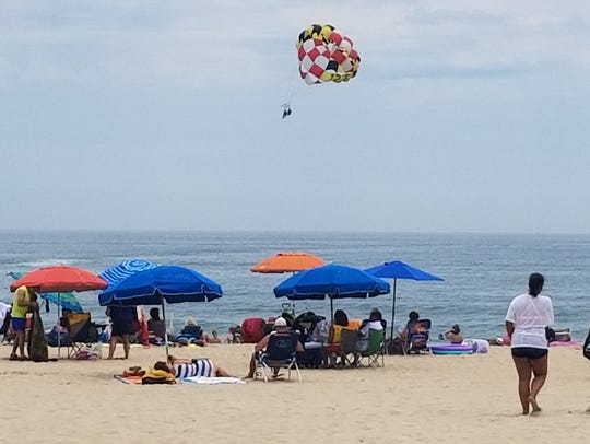 Beachgoers enjoy the sunny weather Sunday in Ocean
