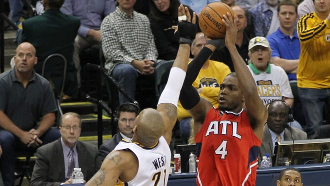 Atlanta's Paul Millsap, right, shoots over Indiana's David West in the third quarter  on Monday night. The Hawks won 107-97.