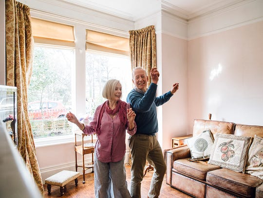 Senior couple are enjoying a dance in the living room
