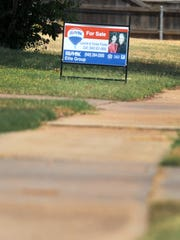 A Remax sign stands in a yard of a home that is for