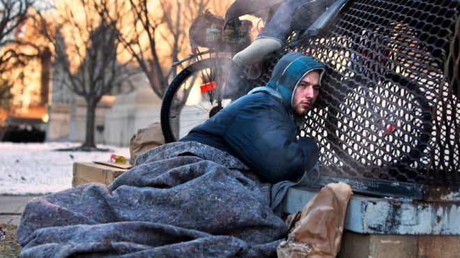 Nick warms himself on a steam grate with three other homeless men by the Federal Trade Commission, just blocks from the Capitol, during frigid temperatures in Washington on Jan. 4, 2014.