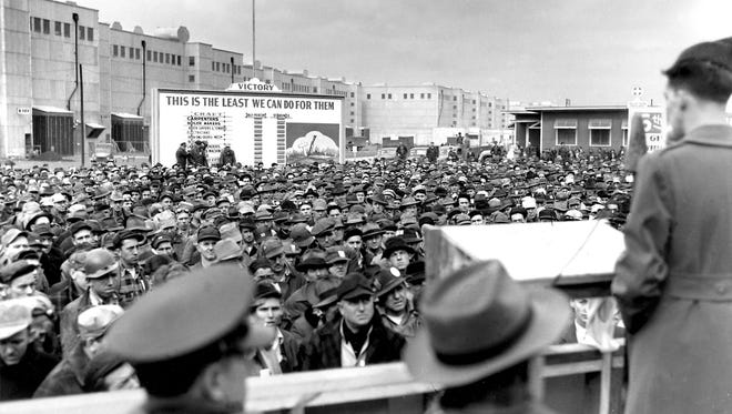 """On Dec. 13, 1944, with World War II still far from over, combat war veterans gave an inspirational talk to hundreds of J.A. Jones Construction Co. workers at a """"Stay on the Job"""" rally outside the K-25 plant in Atomic City, Oak Ridge, Tenn. Note the sign in the background."""