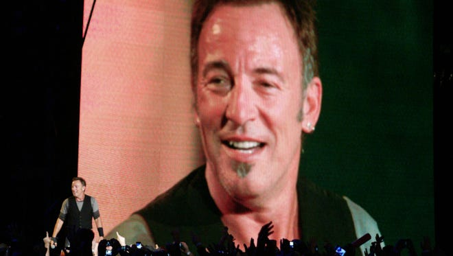 Bruce Springsteen is shown on a big screen in a 2009 performance at Giants Stadium.