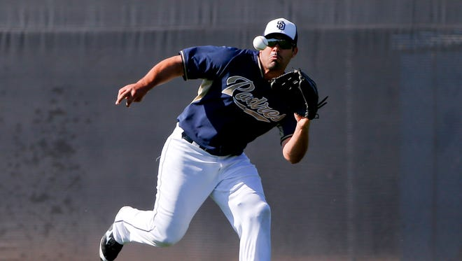 San Diego Padres left fielder Carlos Quentin runs down a line drive during fielding drills for outfielders prior to a spring training baseball game against the Chicago White Sox in Peoria, Ariz. In a trade announced Sunday, April 5, 2015, the San Diego Padres acquired Craig Kimbrel and outfielder Melvin Upton from the Atlanta Braves for outfielders Quentin and Cameron Maybin, plus two minor leaguers and a draft pick.