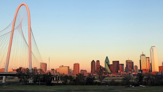 The Margaret Hunt Hill Bridge stands in front of the Dallas skyline.