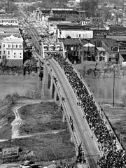 In this March 21, 1965, file photo, Martin Luther King Jr. leads civil rights demonstrators cross the Alabama River on the Edmund Pettus Bridge at Selma, Ala., at the start of a five-day, 50-mile march to Montgomery to press for voter registration rights for African-Americans.