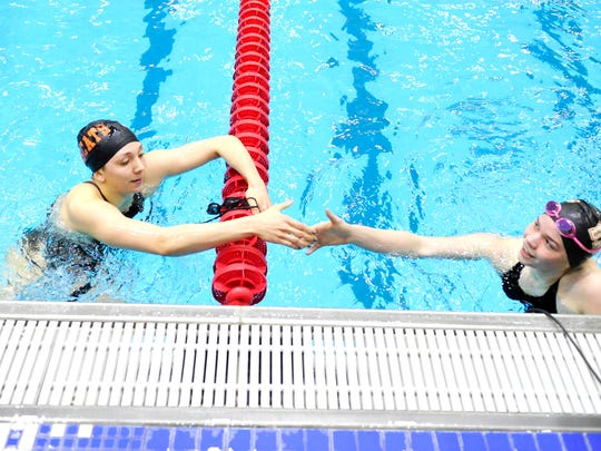 Northeastern's Niki Price, left, shakes hands with Dover's Aniella Janosky after their heat in the 100-yard butterfly Friday during the District 3 Class AAA Swimming Championships. (Daily Record/Sunday News -- Chris Dunn)