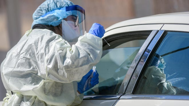 Physician's assistant Natasha Rodriguez prepares to administer a COVID-19 swab test on a drive-through patient Tuesday, April 21, 2020 at Heartland Health Services, 2321 N. Wisconsin Avenue, in Peoria.
