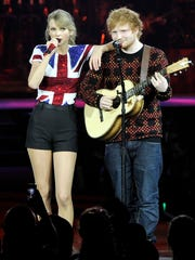 Ed Sheeran, left, takes the stage in London in 2014