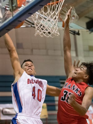 Las Cruces High's Devon Esslinger  goes up for the dunk against Hanks Rick Valverde during the second quarter Tuesday night at Las Cruces High School. The Bulldawgs beat Hanks 48-31, led by 10 points each from Vince Johnson and RJ Brown.