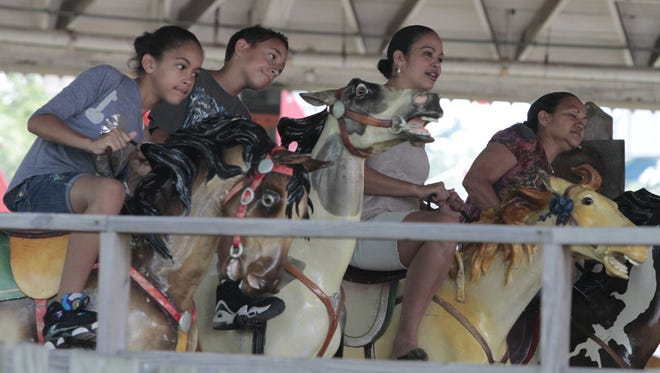 Visitors at Playland amusement park ride the Derby Racer in September 2011.