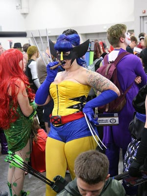 A gender bending cosplayer dressed as Wolverine poses with her cigar at the Salt Lake Comic Con world record event Sept. 25, 2015.