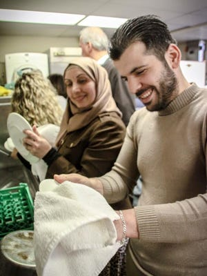 Anis Hamad, 25, a Syrian refugee who now lives in Bloomfield Hills, washes dishes on Dec. 25, 2015, at Christ Church Cranbrook in Bloomfield Hills.
