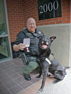 Senior Deputy Jerry Wollenschlaeger and his partner, Yo, after receiving a lifesaving award.