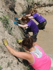 Three women climb out of a mud pit during the 2015