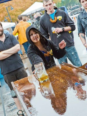 A Northside Oktoberfest participant plays a game of beer slide at the 2013 event.