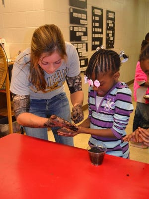Megan VanRuiswyk of the Waupun FFA helps Miracle Gardner of Grantosa Drive Elementary School plant a seed in the Horticulture Session of the Waupun FFA Agriculture Day in Milwaukee.