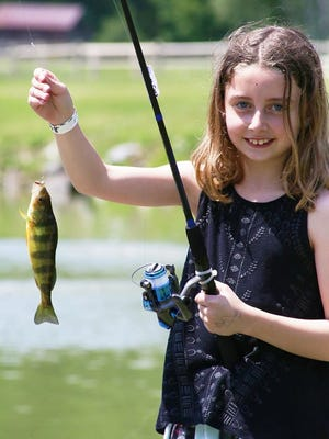 Olivia Marino proudly shows off her catch at Healing Hearts Camp last year.